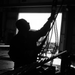 Silhouette of man working with pipe in Nisku